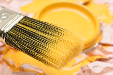Paintbrush and can with yellow paint, closeup
