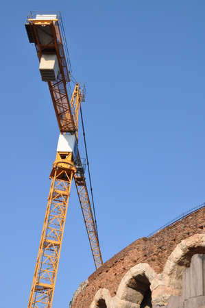 Arena di Verona ancient wall amphitheater with construction crane against blue sky
