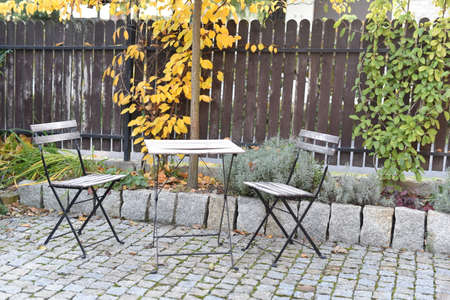 Chairs and table in an autumn garden Imagens