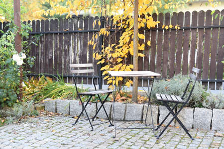 Chairs and table in an autumn garden Imagens - 110239122