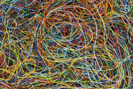 Netwerkchaos van kleurrijke elektrische en telecommunicatiekabels als achtergrond