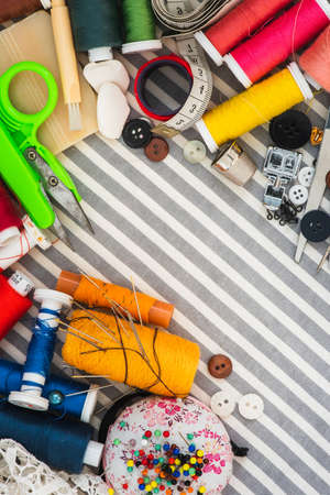 Sewing tools on striped background top view