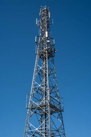 Communication tower with clear blue sky Imagens