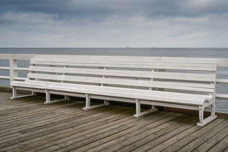 Empty bench on wooden boardwalk at seashore Archivio Fotografico