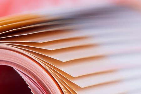 Macro edge of colorful magazine paper with blurred background Archivio Fotografico