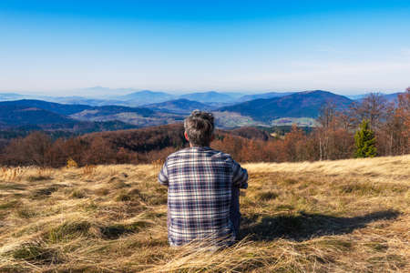 Rear view of lonely man sitting on grassy hill and looking at the mountains