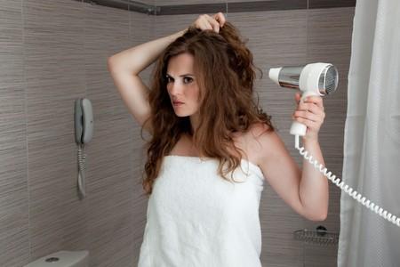 dressed in towel beautiful woman using fen at modern bathroom photo