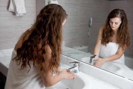 dressed in towel beautiful woman washing hand at modern bathroom photo