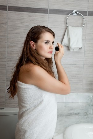 dressed in towel gorgeous woman makeup at modern bathroom Stock Photo - 11640387