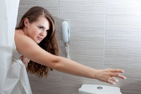 gorgeous woman behind curtain streching for something at modern bathroom photo