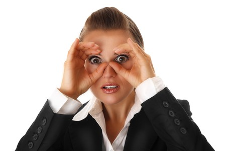 attentiveness: modern business woman making binoculars with hands and looking through isolated on white