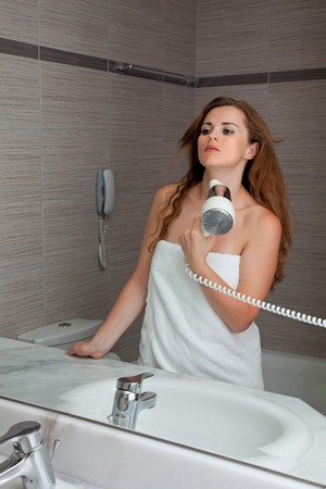 dressed in towel beautiful woman using fen at modern bathroom photo