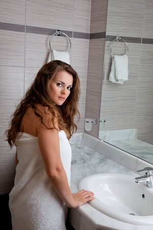 dressed in towel beautiful woman staying at modern bathroom photo