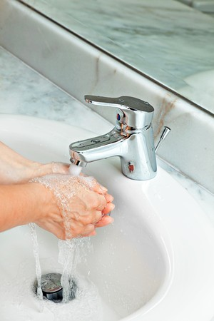 woman washing hands at modern marble bathroom. bubbled water photo
