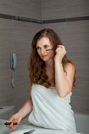 dressed in towel gorgeous woman makeup at modern bathroom Stock Photo - 7635358