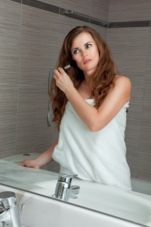 dressed in towel gorgeous woman makeup at modern bathroom photo