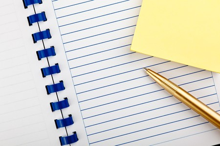 scratchpad: open notebook with placed diagonally ballpoint pen on office desk