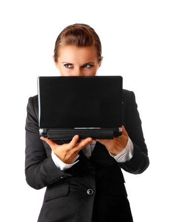 cagey: sly modern business woman suspicious looks out from laptop isolated on white  Stock Photo