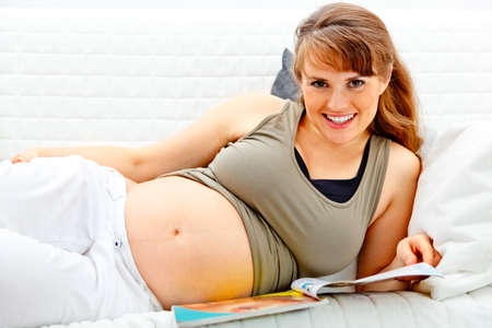 Smiling beautiful pregnant woman relaxing on sofa at home with magazine. Stock Photo - 8144197