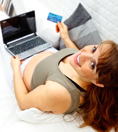 Smiling beautiful pregnant woman on sofa at home with the laptop and a  credit card.  photo