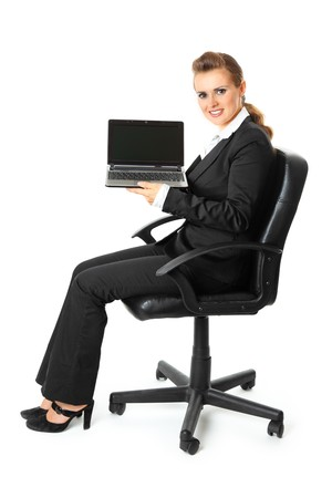 Smiling modern business woman sitting on  chair and holding laptop in hand with blank screen  isolated on white Stock Photo - 8274114