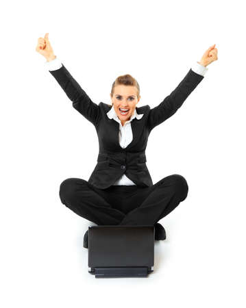 rapturous: Excited modern business woman sitting on  floor and working on laptop isolated on white