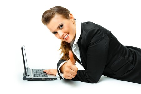 Smiling modern business woman laying on floor with laptop and showing thumbs up gesture  isolated on white  photo