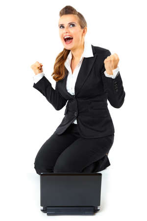 Excited modern business woman sitting on  floor with laptop and rejoicing her success  isolated on white Stock Photo - 8274115