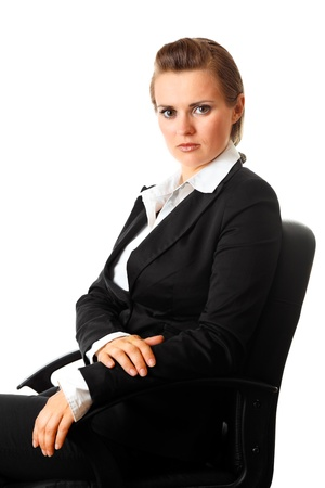 sagacious: Portrait of serious modern business woman sitting on  office  chair isolated on white  Stock Photo