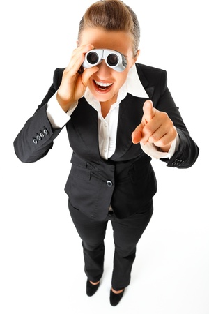 attentiveness: interested modern business woman with  binoculars and  pointing finger at you isolated on white