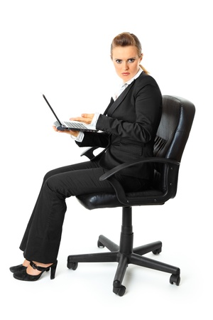 Displeased modern business woman sitting on chair and holding laptop in hand  isolated on white  photo