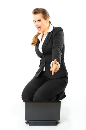 Friendly modern business woman sitting on floor and pointing finger at laptop isolated on white Stock Photo - 8274186