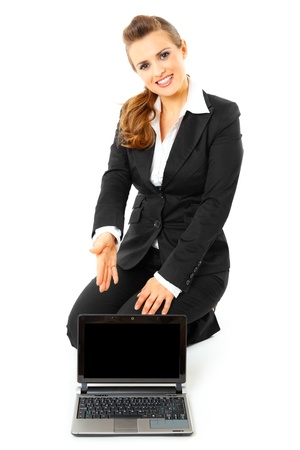 Smiling modern business woman sitting on floor and pointing on laptops blank screen isolated on white