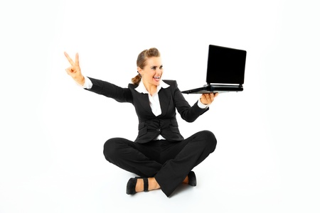 Smiling modern business woman sitting on floor with laptops and showing victory gesture  isolated on white Stock Photo - 8343799