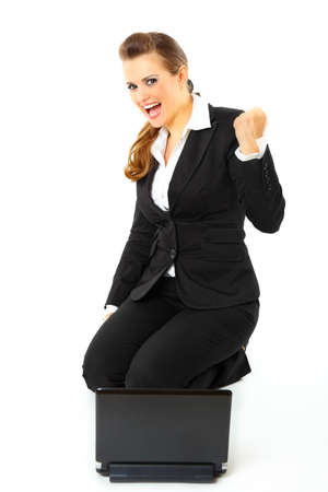 Sitting on floor with laptop excited modern business woman with laptop rejoicing her success isolated on white