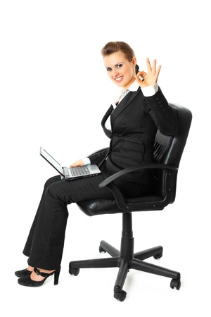 Smiling modern business woman sitting on  chair with  laptop and showing ok gesture isolated on white Stock Photo - 8343867