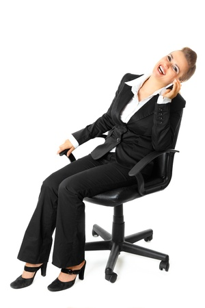 Successful modern business woman sitting on chair and talking on mobile phone  isolated on white