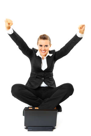 Excited modern business woman sitting on  floor with laptop and rejoicing her success  isolated on white  Stock fotó