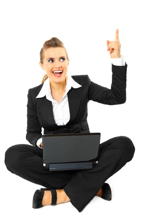Smiling modern business woman got  idea while sitting on floor with  laptop  isolated on white
