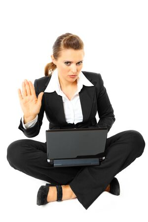 Sitting on floor with  laptop serious modern business woman showing stop gesture  isolated on white Stock Photo - 8343878