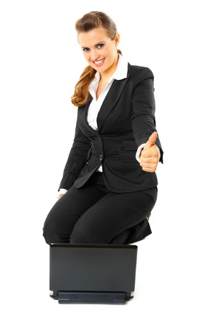 Sitting on floor with laptop smiling modern business woman showing thumbs up gesture isolated on white