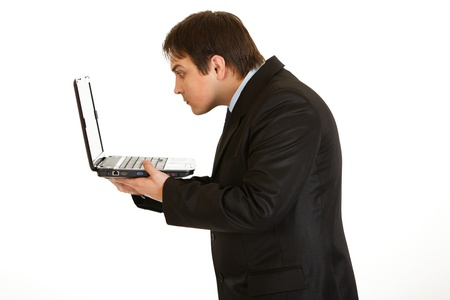 Young businessman amazedly looking in laptops screen isolated on white Stock Photo - 8390361