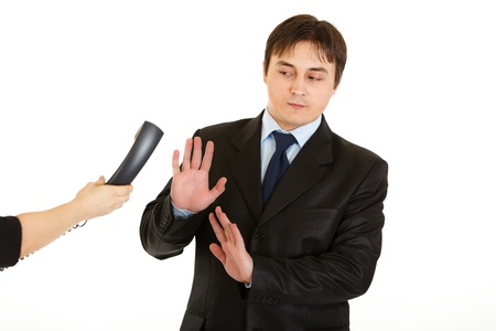 Very busy young businessman refusing to answer on phone call isolated on white  photo