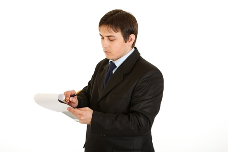Serious young businessman making notes in document isolated on white  photo