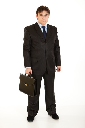 sureness: Full length portrait of young businessman holding  briefcase in hand isolated on white