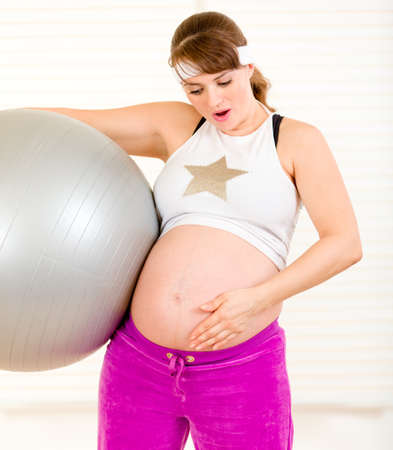 Surprised beautiful pregnant woman  holding  fitness ball and touching her belly at living room  photo