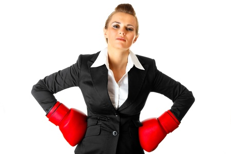 Confident modern business woman holding hands with boxing gloves on hips isolated on white