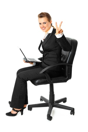 Smiling modern business woman sitting on  chair with  laptop and showing victory gesture isolated on white