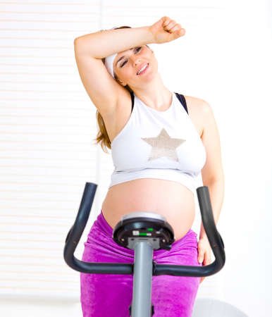 static bike: Pregnant woman sitting on stationary bike and relaxing after work out