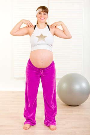haciendo ejercicio: Sonriente y hermosa mujer embarazada haciendo ejercicio en la sala de estar  Foto de archivo